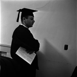 Primary view of object titled '[Graduate holding a commencement program]'.