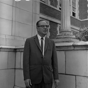 Primary view of object titled '[Dr. Ernest Clifton standing in front of a building]'.