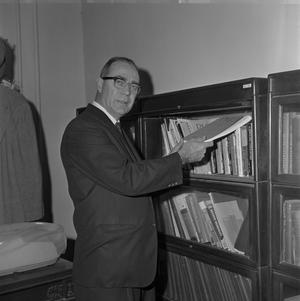 Primary view of object titled '[Dr. Ernest Clifton from the English Department holding a PMLA book]'.