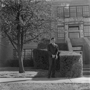 Primary view of object titled '[Male Who's Who student standing in front of building]'.
