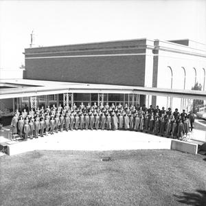 Primary view of object titled '[Grand Chorus standing in a semicircle in front of a building]'.