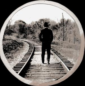 Primary view of [Man walking on train tracks]