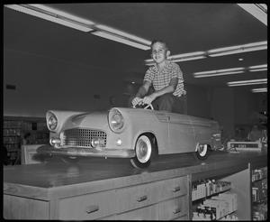 Primary view of object titled '[Boy in a car in Monnig's department store]'.