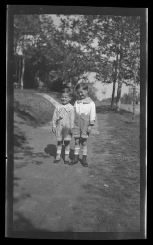 Primary view of object titled '[John and Byrd Williams, III, standing on a sidewalk]'.