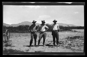 Primary view of object titled '[Three men standing and posing in a desert]'.