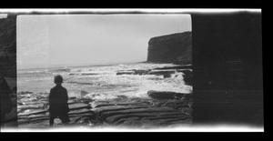 Primary view of object titled '[A boy standing near the ocean, looking toward Point Fermin]'.