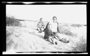 Primary view of object titled '[Irene Williams with two of her sons sitting in sand]'.