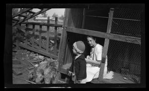 Primary view of object titled '[Irene sitting in a chicken coop with Charles Williams]'.