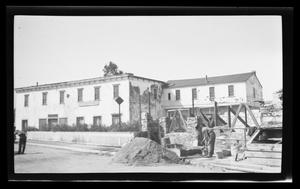 Primary view of object titled '[Man constructing a stone building in front of the Stevenson House in Monterey, California]'.