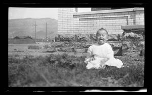 Primary view of object titled '[Photo of a baby sitting in front of a house]'.