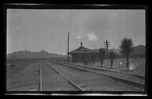 Primary view of object titled '[Two men sit at a train station]'.
