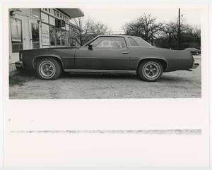 Primary view of object titled '[A 1970s Grand Prix parked outside NT Travel]'.