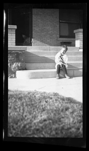 Primary view of object titled '[Photo of a young boy sitting on steps in front of a house]'.
