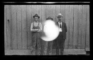 Primary view of [Photo of three men standing in front of a fence]