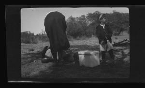 Primary view of object titled '[Irene Williams and Charles Williams cooking outside]'.