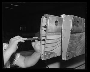 Primary view of object titled '[Bell employee working on the main rotor blade of the XH-40]'.