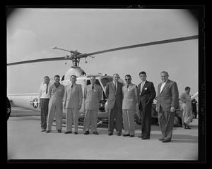 Primary view of object titled '[Colonel John L. Inskeep and others, standing in front of an XH-40 helicopter]'.