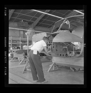 Primary view of object titled '[Bell employee working on the nose assembly of the XH-40]'.