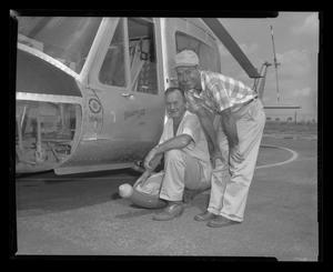 Primary view of object titled '[Two Bell employees pose near an XH-40]'.