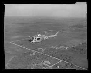 Primary view of object titled '[XH-40 #3 in flight over the Hurst plant]'.
