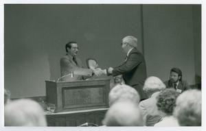 Primary view of object titled '[Two Men Shaking Hands with Presentation of Plaque]'.