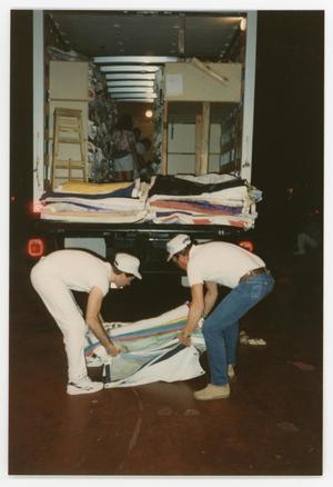 Primary view of object titled '[Two Volunteer Workers Unloading AIDS Memorial Quilts]'.