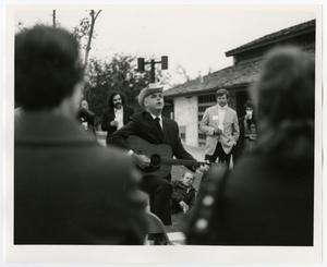 Primary view of object titled '[Charles W. Cockran Plays Guitar as Crowd Watch]'.