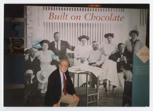 "Primary view of object titled '[Man Posing with ""Built on Chocolate"" Poster]'."