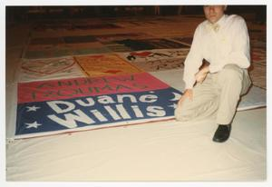 Primary view of object titled '[Man Kneeling at AIDS Memorial Quilt for Andrew Tzoumas and Duane Willis]'.
