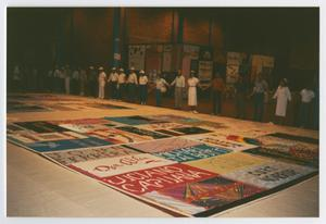 Primary view of object titled '[Members Standing in Unity While Viewing AIDS Memorial Quilts]'.
