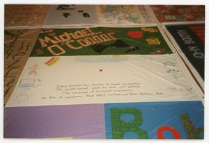 Primary view of object titled '[Quilt Section with Panels Dedicated to Michael O'Connor and an Anonymous Brother]'.