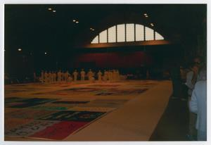 Primary view of object titled '[Members/Viewers Standing Around AIDS Memorial Quilts]'.