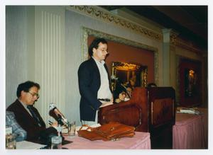 Primary view of object titled '[Man Speaking at Podium with a Panel]'.