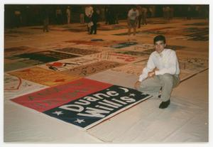 Primary view of object titled '[Man Kneeling Beside Quilt Panel for Duane Willis]'.