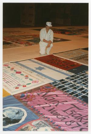 Primary view of object titled '[Man in White Kneels Beside AIDS Memorial Quilt Section]'.