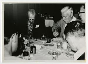 Primary view of object titled '[Men Sitting at a Table Having Dinner]'.