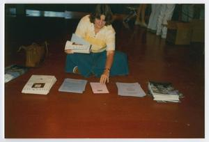 Primary view of object titled '[Woman Seated on Floor Organizing Fliers for Names Project Tour]'.