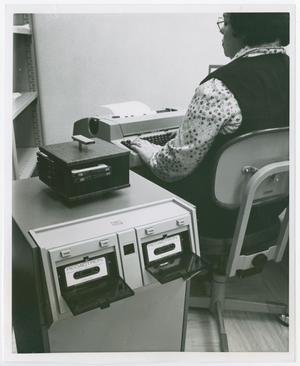 Primary view of object titled '[Woman Processing a Cassette Tape]'.