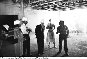 Primary view of object titled '[Several Guests with Hard Hats in Empty Building]'.