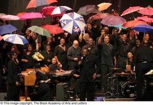 Primary view of object titled '[Soloist Singing in Front of Chorus with Umbrellas]'.