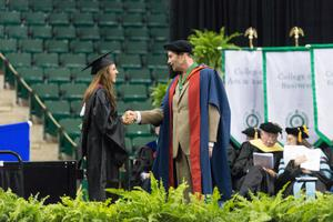 Primary view of object titled '[Female Graduate and Dean Shaking Hands at the Commencement Ceremony]'.