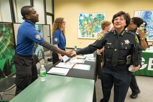 Primary view of object titled '[Police officers shake student's hand the LGBTQIA Career Fair, 3]'.