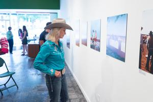 Primary view of object titled '[Cowgirl in Blue Examining Exhibit Photographs]'.