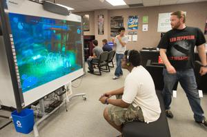 Primary view of object titled '[Student plays video game in the UNT Media Library]'.