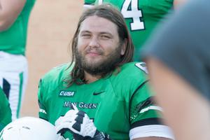 Primary view of object titled '[UNT Football Player Looking For Photo]'.