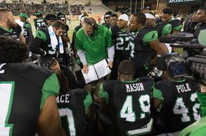 Primary view of object titled '[Mean Green Football Team in a Huddle]'.