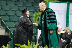 Primary view of [President Neal Smatresk on stage with an Undergraduate Student]