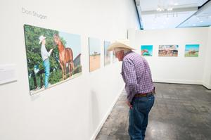 Primary view of object titled '[Cowboy Examining Photograph at Exhibit]'.