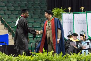Primary view of object titled '[Male Graduate Student Shaking Hands with Dean]'.