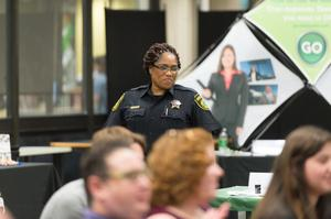 Primary view of object titled '[Police officer standing at the LGBTQIA Career Fair, 2]'.